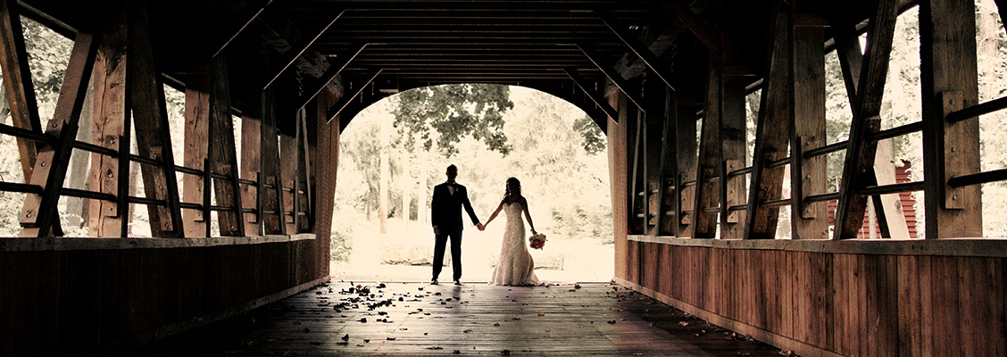 Bride and groom stand under a bridge.