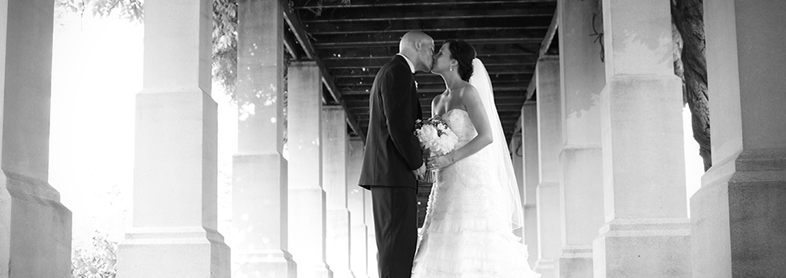Bride and groom kiss under pillars.