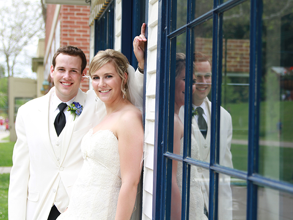Couple outside in wedding gown and suit.