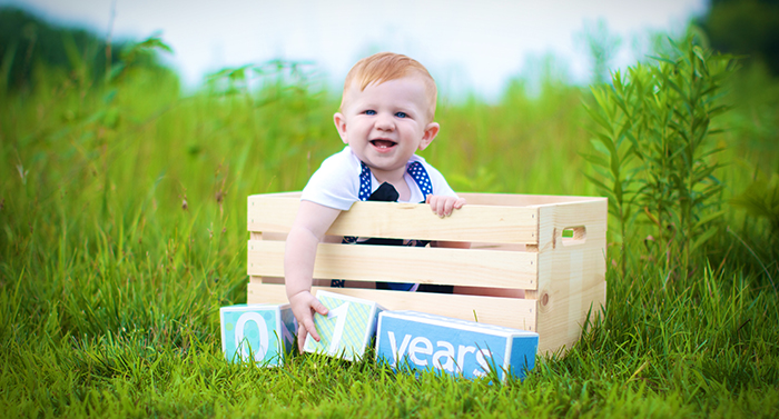 Baby in crate with one year old sign.