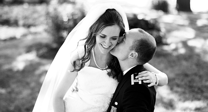 Bride sits on groom's lap while he kisses her cheek.